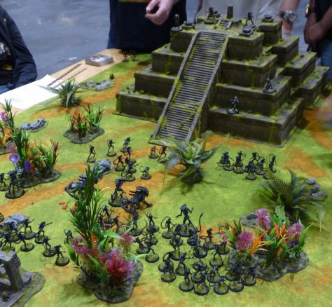 An Alien horde rushing towards a group of Predators on a jungle pyramid