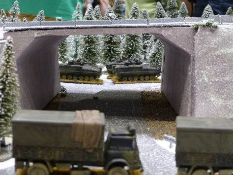 Columns of trucks and light tanks passing by a bridge