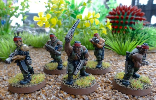 Four soldiers in green jungle fatigues with laser rifles lead by a Sergeant with sword and pistol