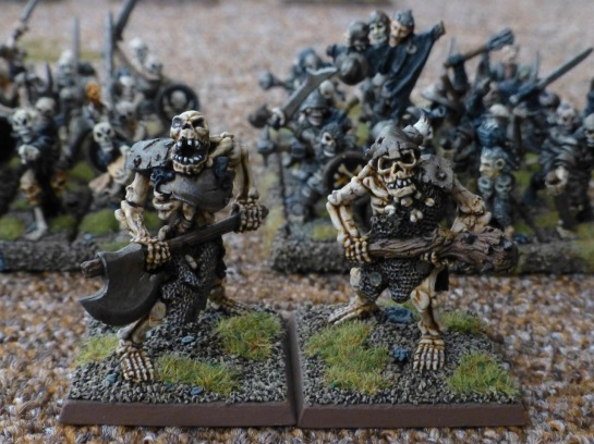 Two skeletal ogres standing in front of units of skeleton warriors