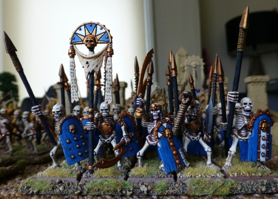 Front view of a regiment of skeletons with spears, a banner and a horn blower