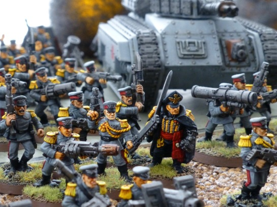 Commissar and infantry of the Mordian Iron Guard with a Hellhound tank in the background