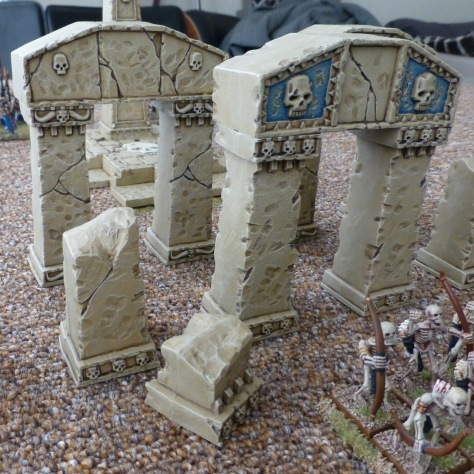 Broken columns and arches of sandstone with skeletal archers in front