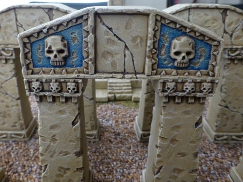 An arch of sandstone blocks decorated with carved skulls and with faded blue panels