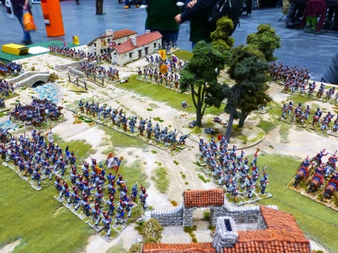 Napoleonic troops on a battlefield with a small river and countryside buildings
