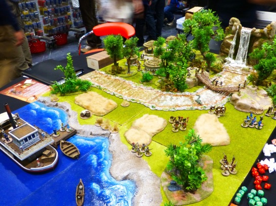 A small wargames table with a river and steamboat in front and a jungle scene with waterfall and small huts
