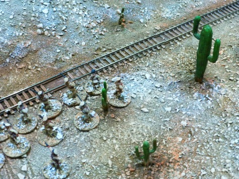 A column of uniformed troops advancing along a train line through a desert with cacti