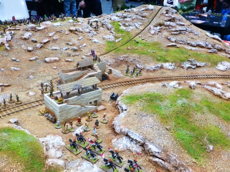 A railroad line and small station in a rocky landscape with scattered infantry and cavalry units