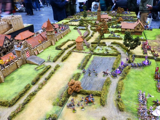 View of a wargaming table with city walls on the left and an army advancing through the countryside from the right