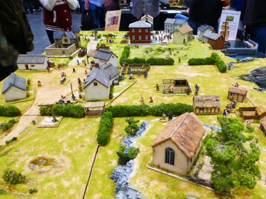View over a wargaming table with scattered buildings, hedgerows and pockets of civilians going about their business