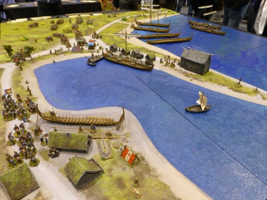 Wargaming table showing a beach with Viking longships close to a village