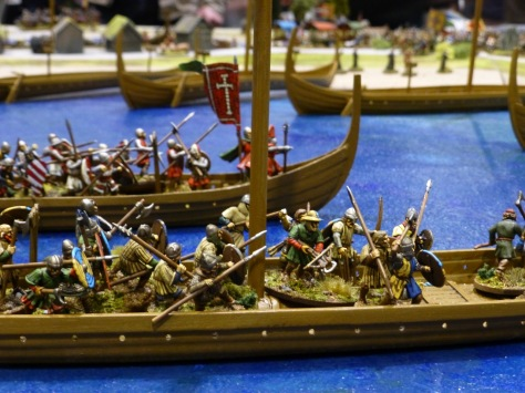 Close-up view of two Viking longships manned by warriors with shields and spears