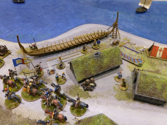 Cavalry passing through a small settlement on the coastline with a longship under construction