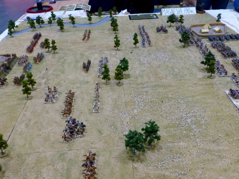 Wargaming table with battle lines of cavalry and infantry advancing towards each other over a wide open fields with scattered trees