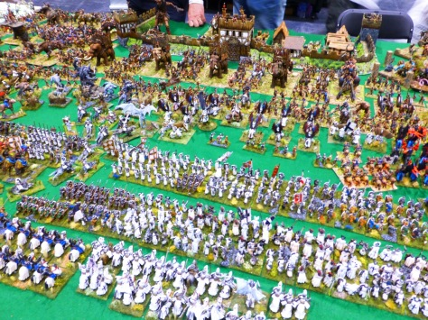 Large regiments of knights and foot soldiers clad in white meeting a Barbarian horde in front of a wooden fort