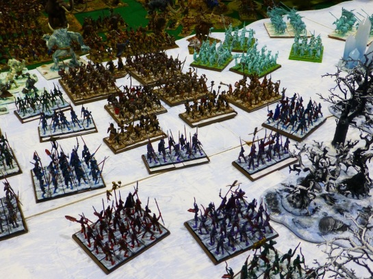 A snowy landscape with regiments of spearmen wearing dark armour, units of etherial troops and troll sized monsters