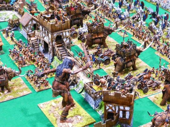 View from behind a wooden palisade with towers and a giant, chariots, war mammoths and Barbarian infantry