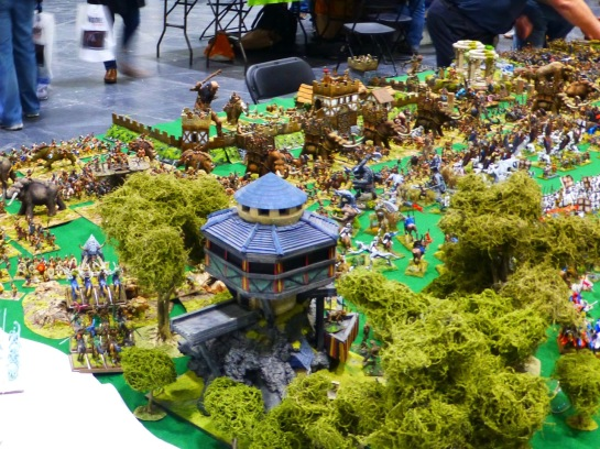 View over a wooden tower in a forest onto a Barbarian army with war mammoths and other beasts