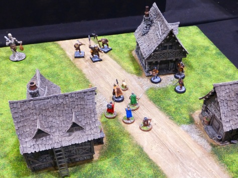 A small wargaming table with three houses and a band of adventurers running into a group of monstrous creatures