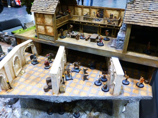 Cutaway of a medieval style house with a basement and cellar floor, all containing groups of heroes fighting against evil creatures