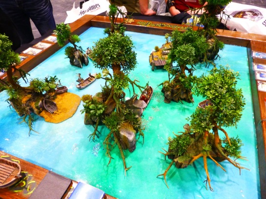 A small gaming table with little islands in a crystal blue lagoon and fantasy figures fighting around row boats