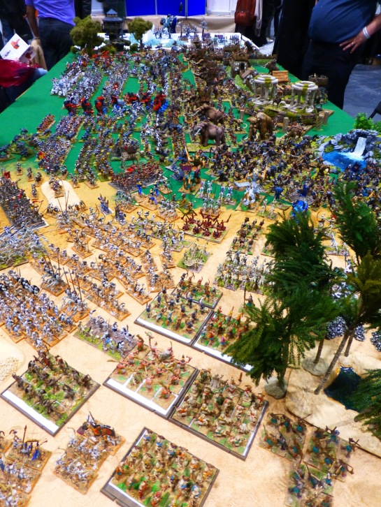 Large wargaming table with a transition from desert to ice landscapes and hundreds of miniatures packed in close formation