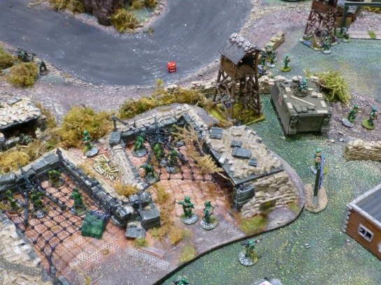 Two artillery emplacements on a river bank with a watchtower and parked APC