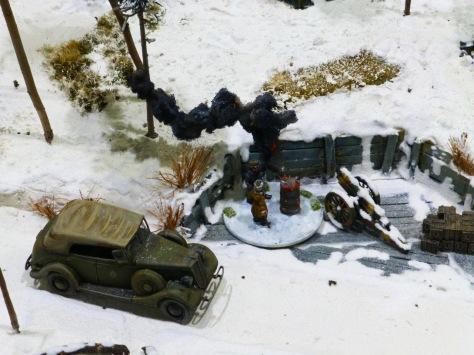 Small winter scene with a staff car, a field gun and crew standing by a barrel fire