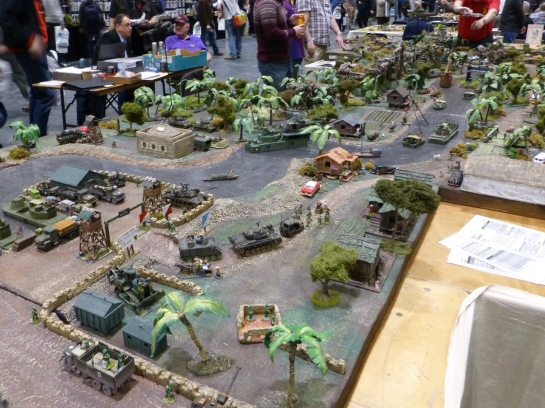 View of a large wargaming table in multiple sections with a river through jungle and military camp in the foreground