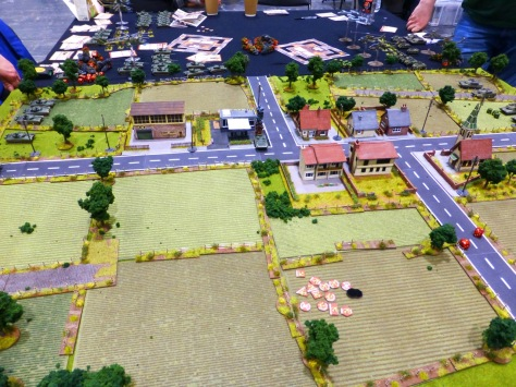 A wargaming table with fields, a crossroads with houses and tanks advancing from both ends