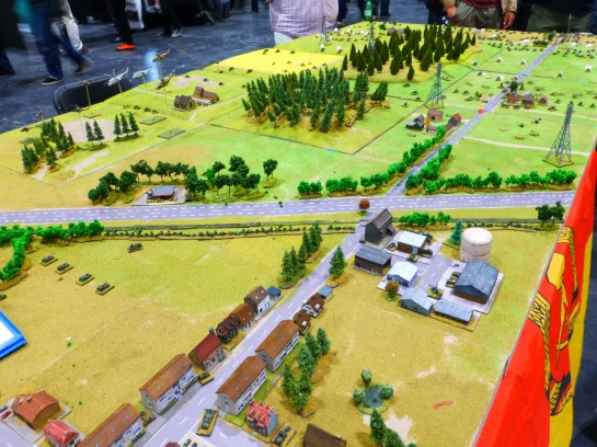 A large wargaming table in 6mm scale with a village and open countryside in the background