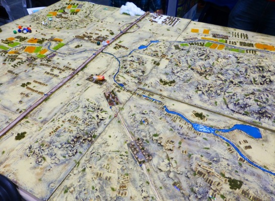 Large wargaming table with mountainous desert terrain and mechanised armies in 3mm scale