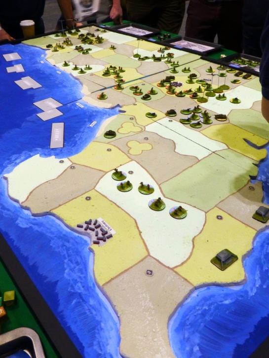 A boardgames style set up showing the Normandy coastline and army tokens occupying sections of the terrain
