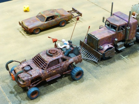 Closer view of converted model cars with rusted and painted bodywork