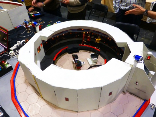A round model of a command bridge with Star Trek action figures placed inside