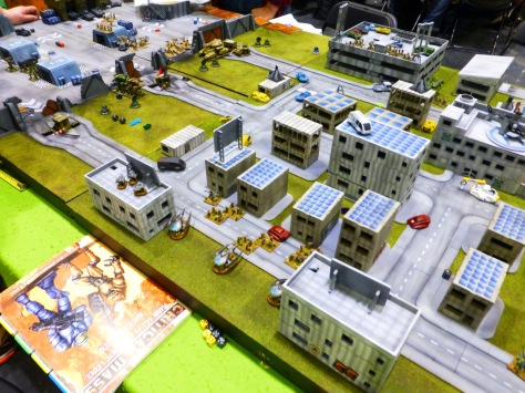 A wargaming table with a model city of high rise buildings and various vehicles and stands of infantry
