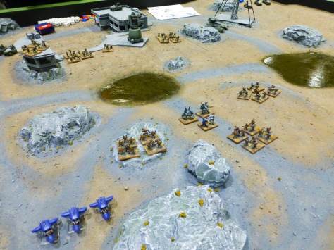 Model landscape of desert and rocks with swampy areas and some concrete buildings contested by two small forces of infantry and futuristic vehicles