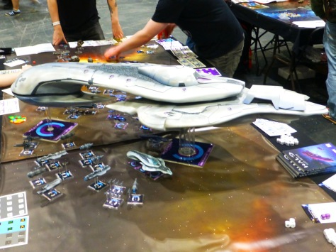 Small space ships on a star field gaming table surrounding a much larger craft