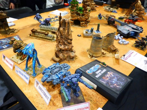 A wargaming table with desert terrain and abandoned industrial buildings and various large mech style war machines