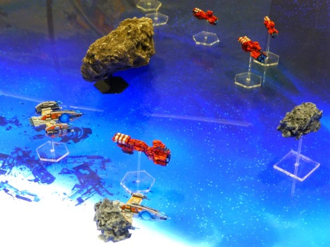 Red and grey space ships amongst asteroids on an underlit blue gaming table