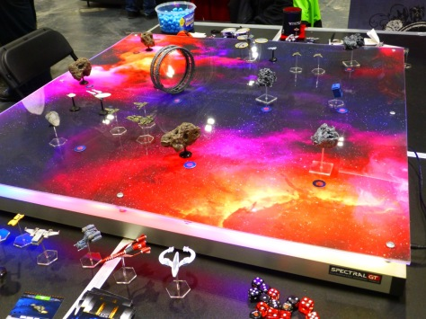 A gaming table showing a backdrop of dark space and red nebulas lit from underneath and with a variety of spacecraft and asteroids placed on top
