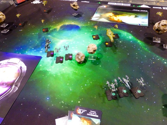 Two fleets of opposing spacecraft on a dark blue gaming table with stars and a green nebula