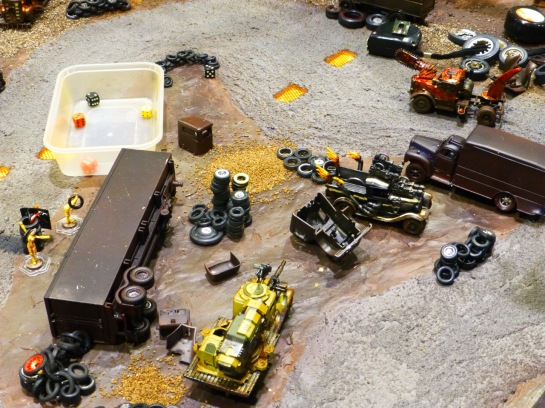 A muddy racing track with converted car models, tire stacks and wrecks