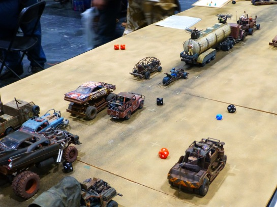 A desert gaming table with scale model cars converted in post-apocalyptic style