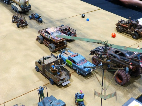 A gyrocopter hovering over models cars shown in pursuit of a tanker