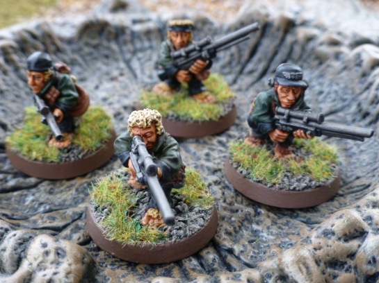 Four Hobbit sized figures with rifles inside a muddy crater