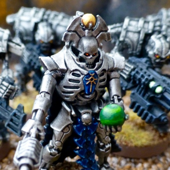 Close up of a robotic warrior with a skull face holding a green orb in his left hand