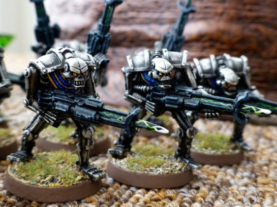 Three silver coloured metal robots in the shape of skeletons armed with black rifles crackling with white green energy