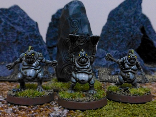 Miniature models of three humanoid creatures with fish-like features