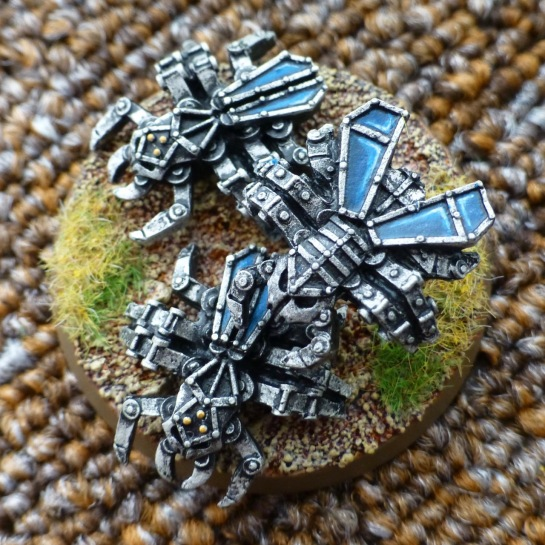 Three beetle shaped metallic drones with blue wings
